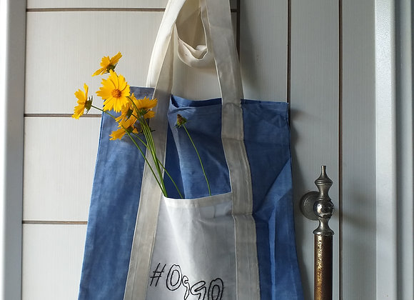Blue handmade hand-dyed cotton reusable shopping bag with pocket and yellow coreopsis flowers on white door knocker.
