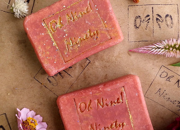Two Oh Nine! Ninety crimson glitter soaps with gold logo stamp surrounded by flowers on brown logo-stamped paper.