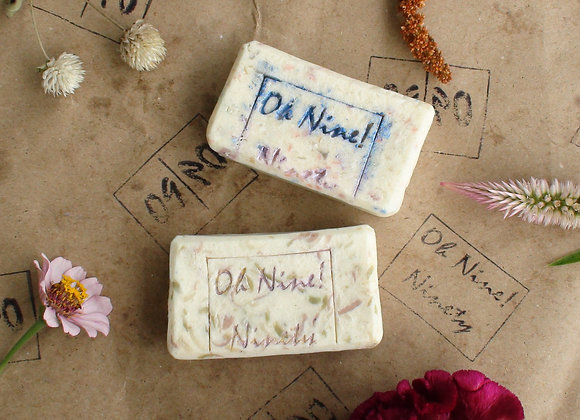 Oh Nine! Ninety 09! celebrations soap set on brown logo-stamped paper surrounded by flowers.