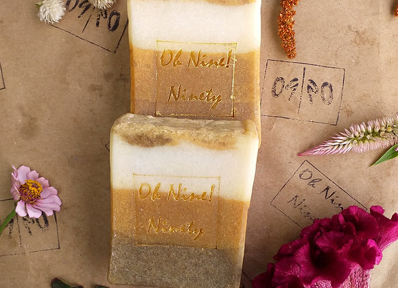 Oh Nine! Ninety handmade natural Earth Layers soap set on brown logo-stamped paper surrounded by flowers.