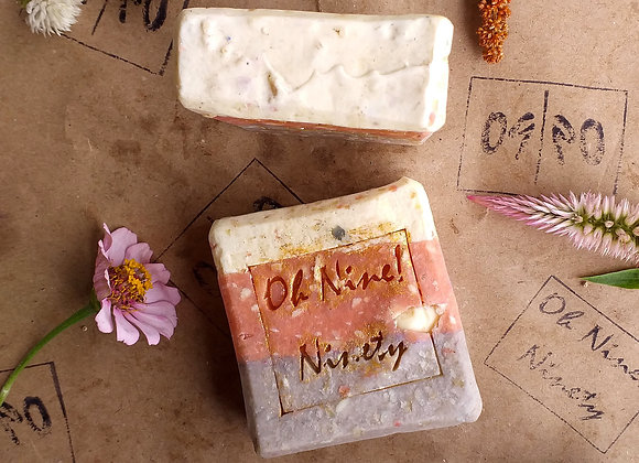 Two Oh Nine! Ninety Confetti Love handmade natural soap bars surrounded by flowers on brown logo-stamped paper.