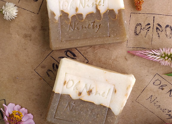 Two Oh Nine! Ninety handmade natural moringa waves soaps surrounded by flowers on brown logo-stamped paper.