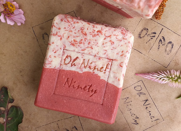 Red and cream Oh Nine! Ninety handmade Raining Miracle soap on brown logo-stamped paper.
