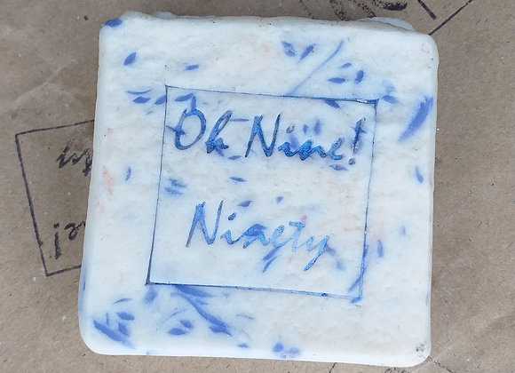 Oh Nine! Ninety white and blue confetti handmade natural Lilac Heaven soap with logo on brown paper.