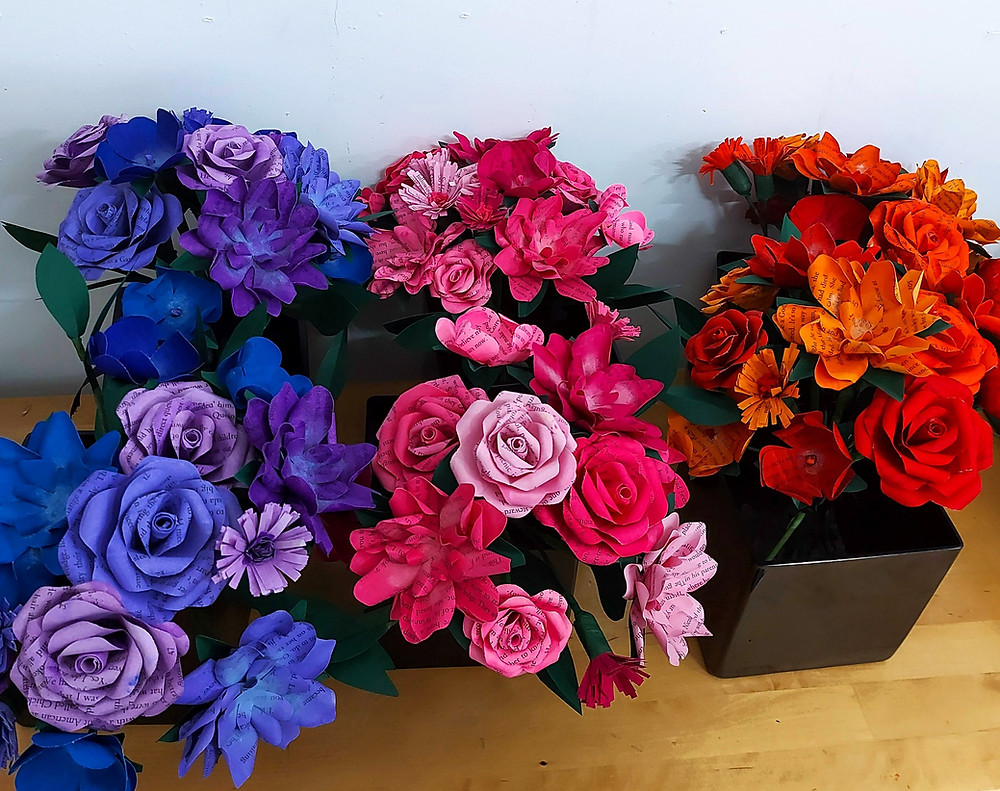 Six brightly coloured paper flower displays in black cube vases. The flowers are a mix of roses and summer flowers, made from recycled book pages. Two vases are blue and purple shades, two are pink shades and two are orange and red shades.