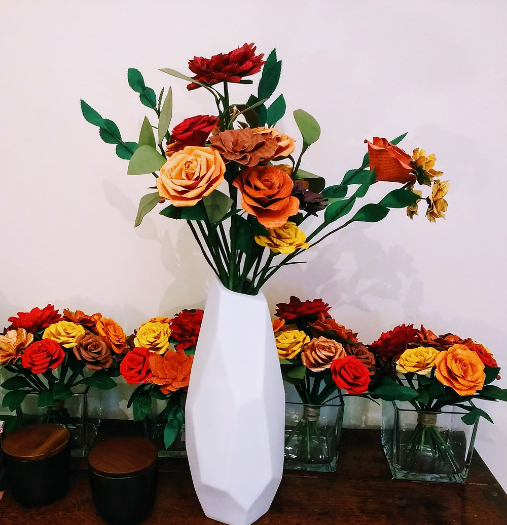 Large white vase containing paper flowers in shades of orange, red, copper and brown. Behind the large vase is a row of smaller cube displays in matching colours.