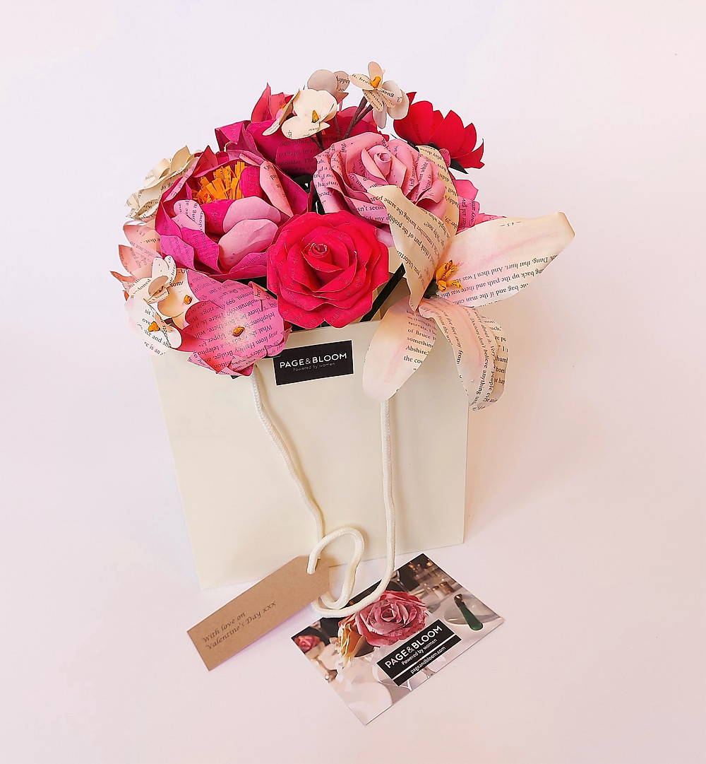 A floral gift bag, containing paper flowers in shades of pink and cream.