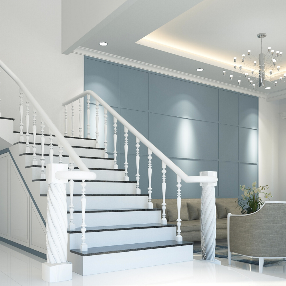 White grand staircase next to a sitting room with a blue-grey accent wall and modern light fixture.