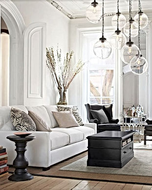 High ceiling living room with globe penant lights and white sofa
