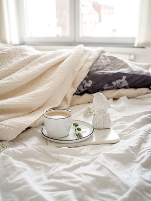 Tea on a tray on an unmade bed