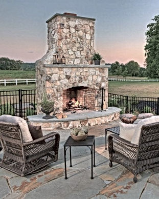 Outdoor fireplace with 2 empty large chairs