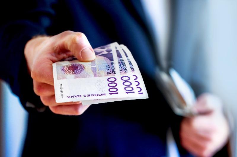 Man handing Norwegian bank notes - The NOK