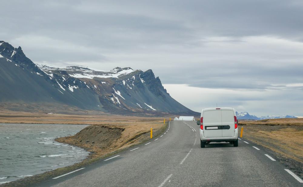 Campervan vista desde atrás circulando por un camino al lado de un río en Islandia