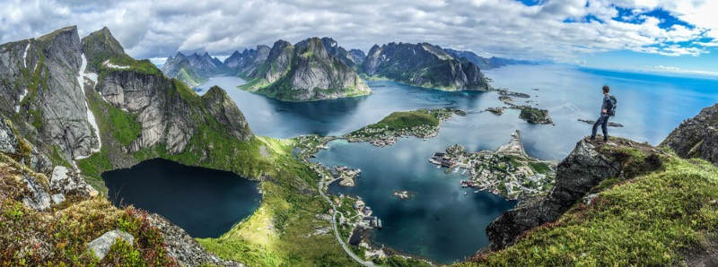Panoramic view of Lofoten with a tourist at the tip of a cliff - Top 10 tourist destinations in Norway