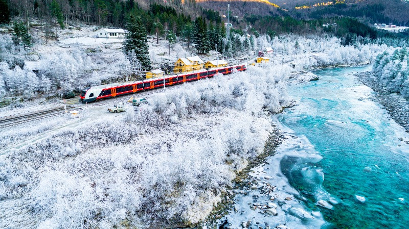 Train Oslo-Bergen in a snowy mountain by the river - All about Bergen, Norway