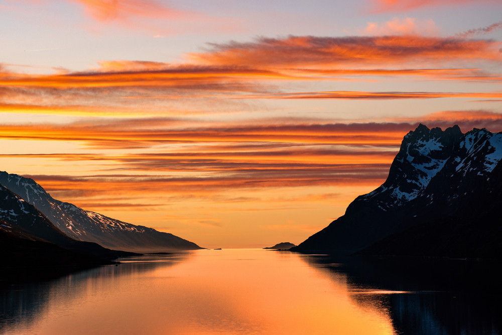 Beautiful orange shades in a lake surrounded by mountains - Midnight sun in Norway