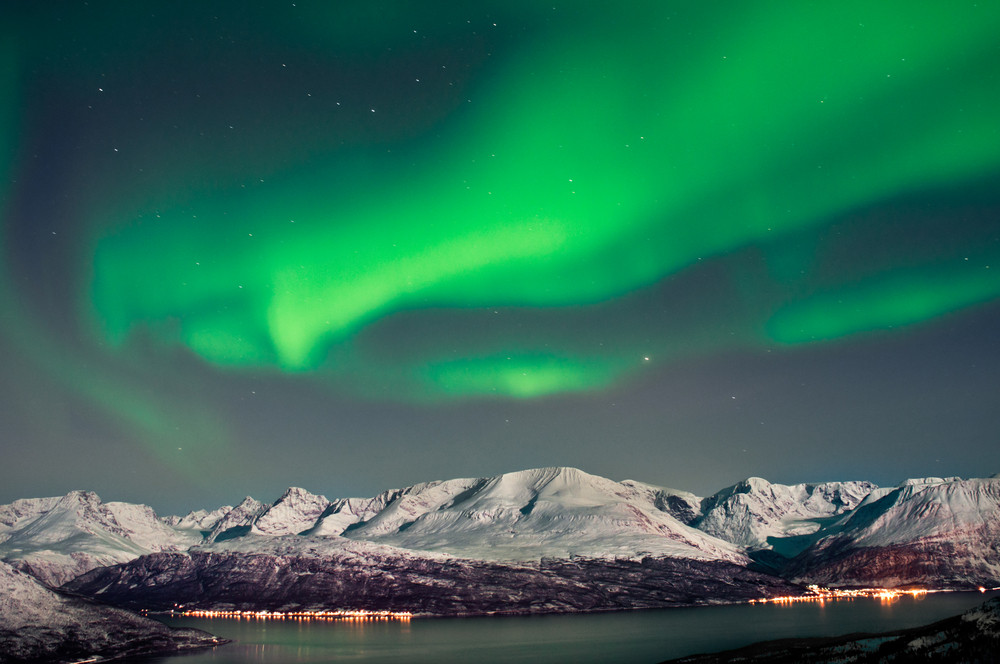 Aurora Borealis dancing on top of snowy mountains - top 10 tourist destinations in Norway