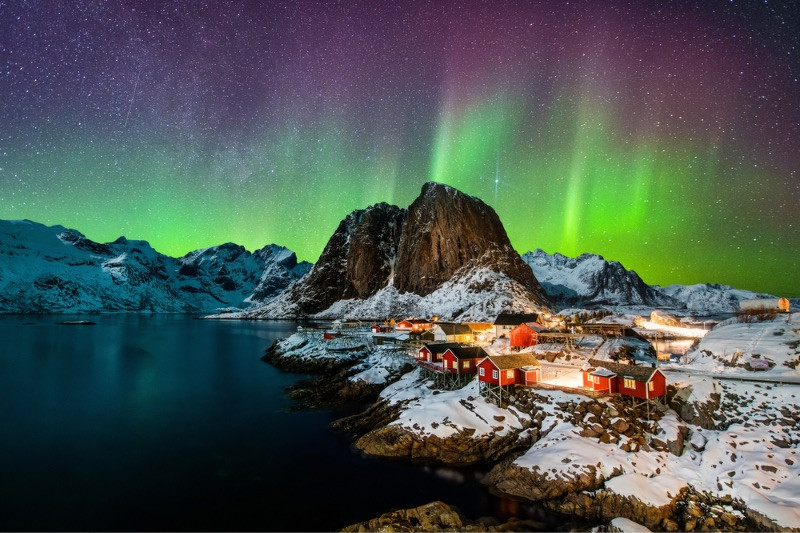 A show of the Northern Lights in Norway, with a coastal town in the foreplan