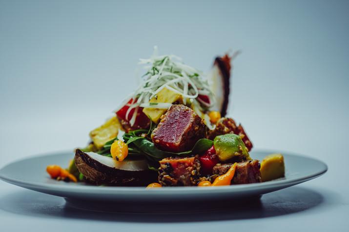 Tuna Poke Salad in a Coconut Shell with Peppadews over Greens