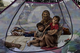 displaced-afghan-family-sit-tent.png