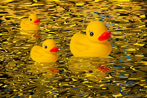 """Afternoon Delight"" Photograph of rubber duckies swimming in brilliant yellow reflecting water nearing sunset."