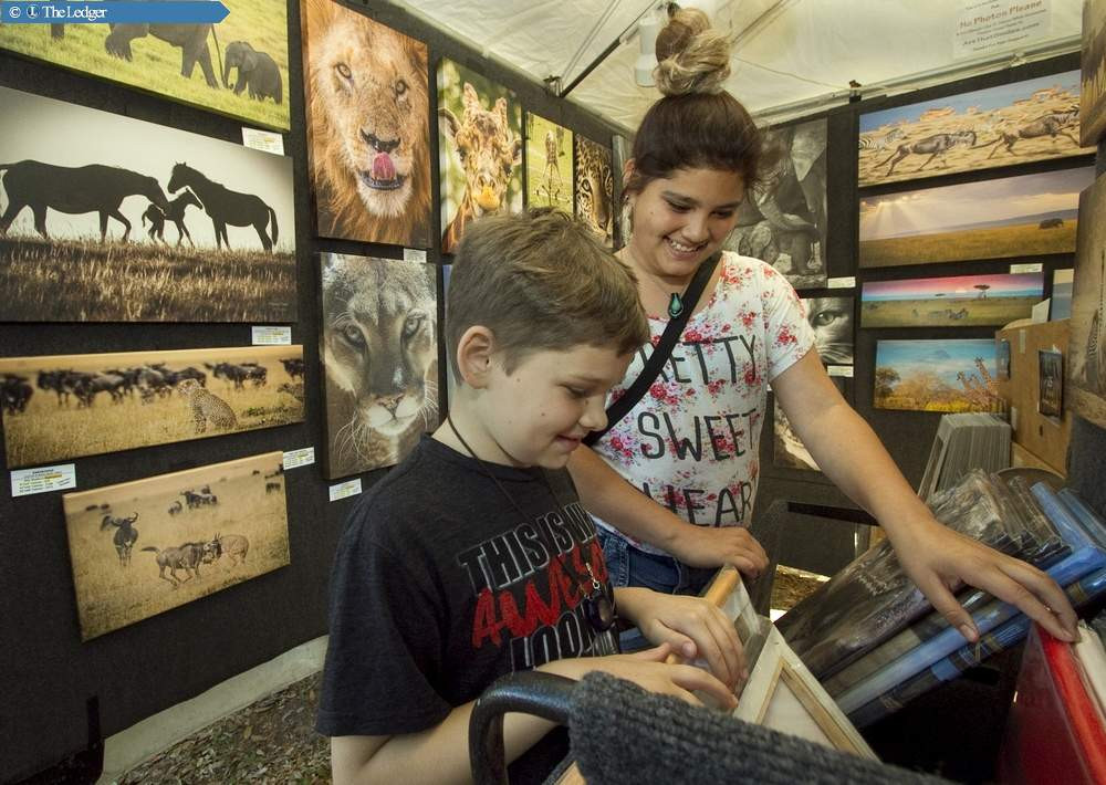 MICHAEL WILSON | THE LEDGER Lake Wales residents Gavin Stanley, 8, left, and his sister Samantha Kitchene, 13, look through the whimsical animal photo print bins of Clearwater artist, John Hartung during the 45th annual Lake Wales Arts Festival at Lake Wailes Park this past Saturday afternoon.
