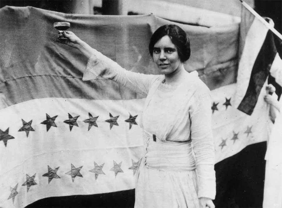Alice Paul raising a glass in from of a flag.