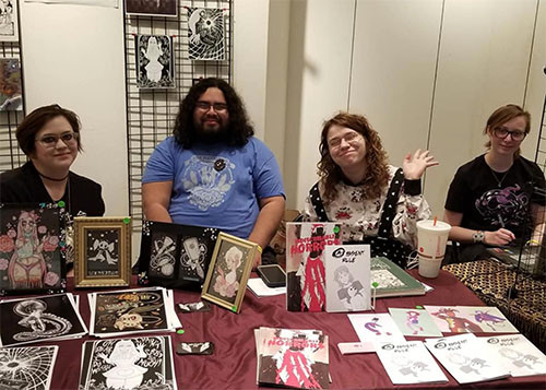 Four people sitting at table smiling at the camera. The table is covered in comics and other artwork for sale.