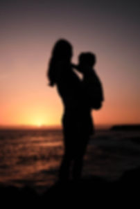 Eine Mutter steht bei Fotoshooting mit ihrem Sohn auf dem Arm vor dem Sonnenuntergang und genießt das Zusammensein mit der Familie.