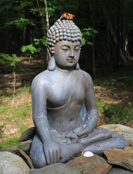 Statuary of Buddha sitting on a large boulder at Sky Meadow Retreat in Vermont