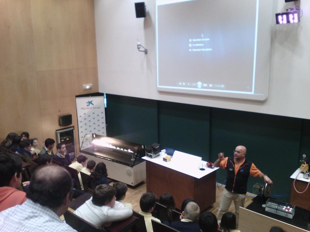 El monitor explicant el tub de Rubens, on es mostren els harmònics amb foc en un tub de gas al passar la música al seu través