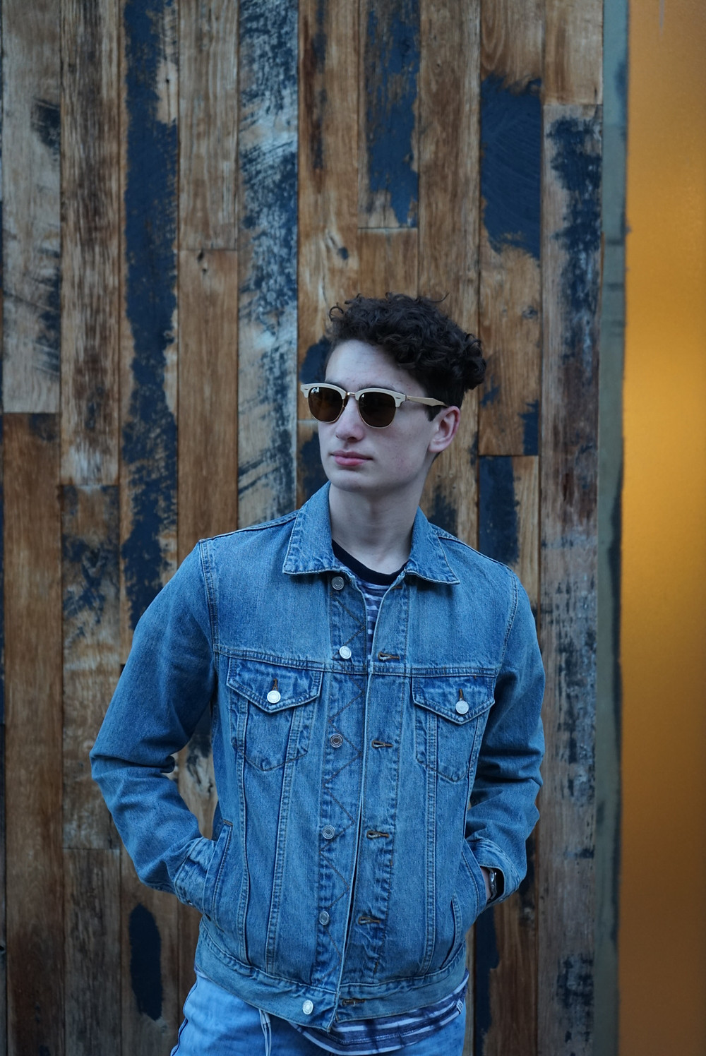 This is a portrait of Brandon Sağlam. In it, he wears a denim jacket, fully buttoned up. He has his hands in his pockets, and is staring off in the distance with shades. He's wearing a striped shirt under. The backdrop seems to be a wooden wall or fence.