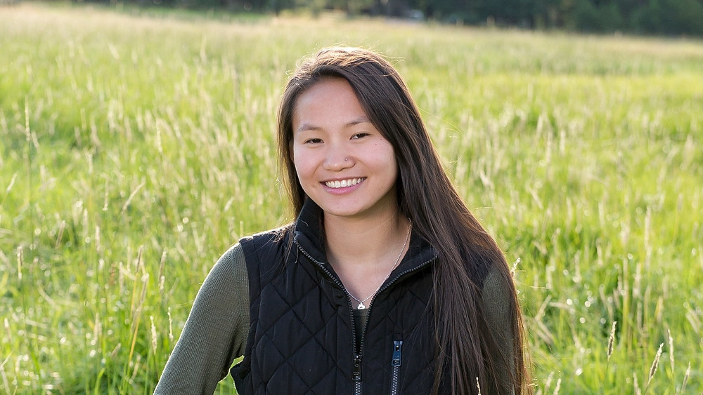 This is a horizontal portrait of Maya Siegel, an Aspirants Magazine feature. In this picture, she is wearing a dark green long sleeved shirt with a black vest over it. She is standing in a field, where the grass is a light green, bordering on yellow.