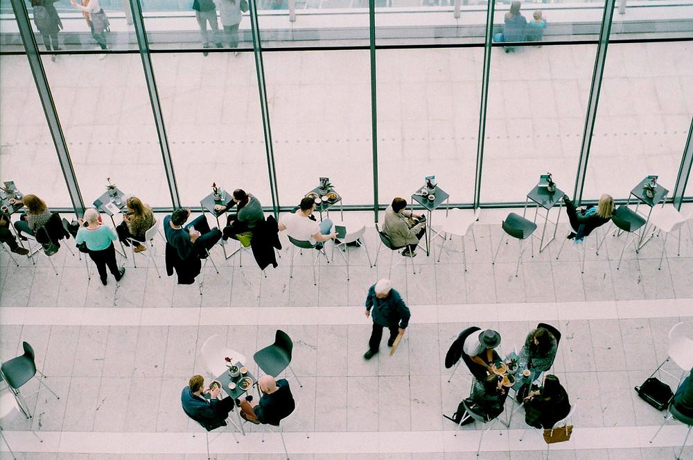 ludzie siedzący przy stolikach z kawą