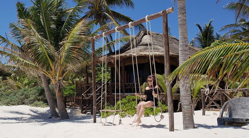 huśtawki, palmy i bungalowy na plaży w Tulum w Meksyku
