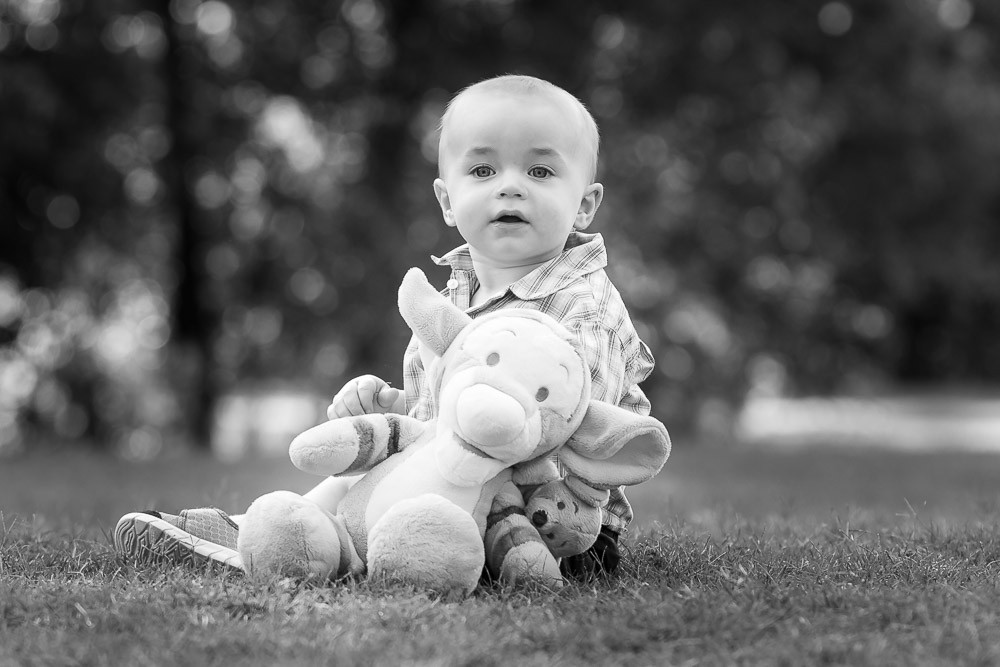 1 year old boy in a chair holding a stuffed animal