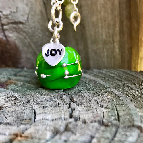"""Green with transparent green encased bead and silver dots with """"joy"""" charm"""