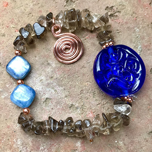 Transparent cobalt blue ohm stamped lampwork bead, strung with Smokey topaz