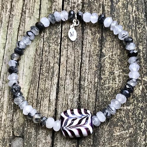 Black and white raked bead strung on rutilated tourmaline quartz