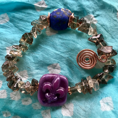 Fleur de lis stamped lampwork bead, purple. Strung with Smokey topaz and lapis