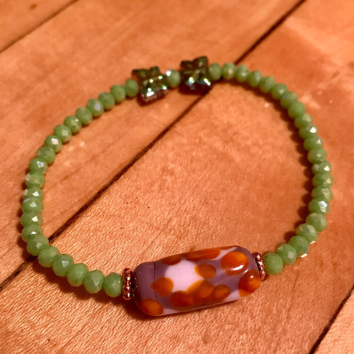 Purplish lampwork bead with green spacers