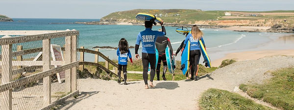 group-walking-down-for-surf-lesson-on-Gw