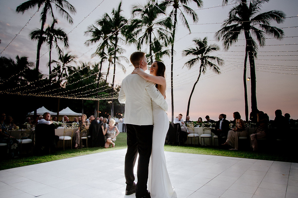 Bride and Groom first dance under twinkle lights on white dance floor