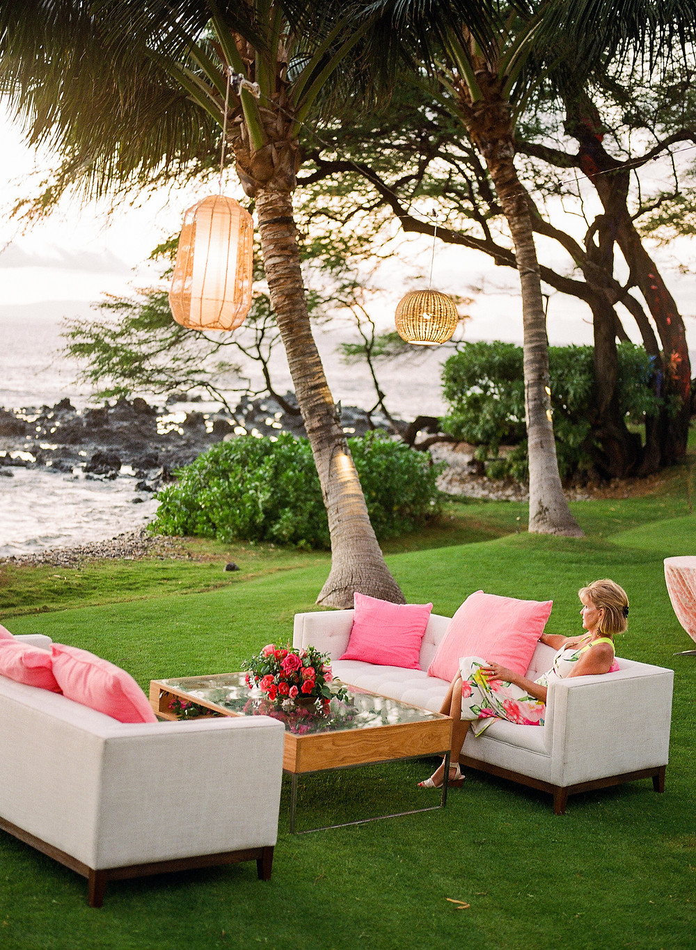 White lounge furniture cocktail hour decor with hanging lights oceanfront on Maui