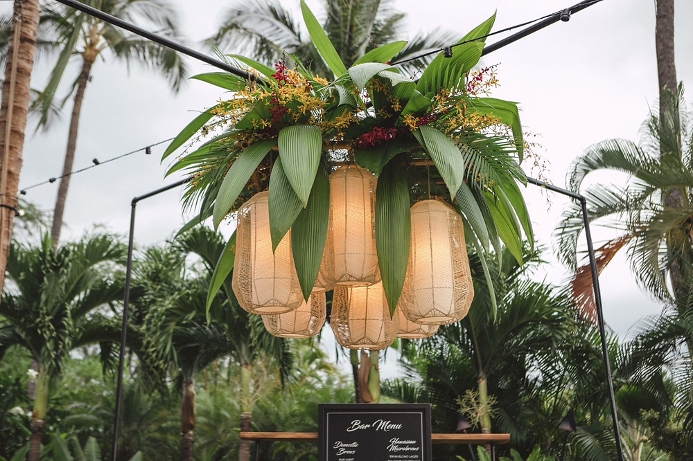 Custom lantern lighting over bar with tropical flowers