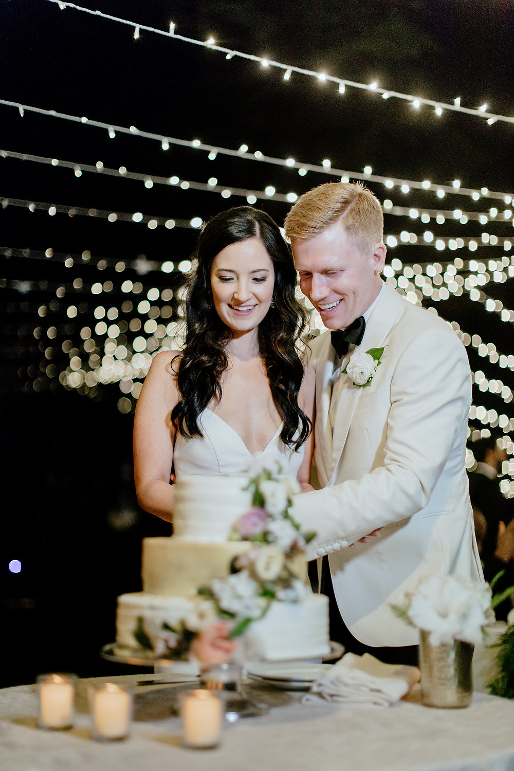 Bride and Groom cutting cake under white twinkle lights