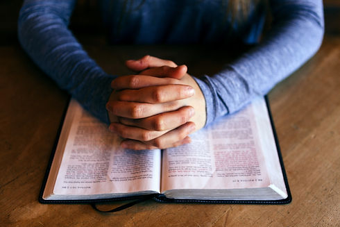 Hands folded over open Bible
