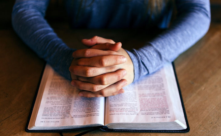 Man's hands folded over open Bible