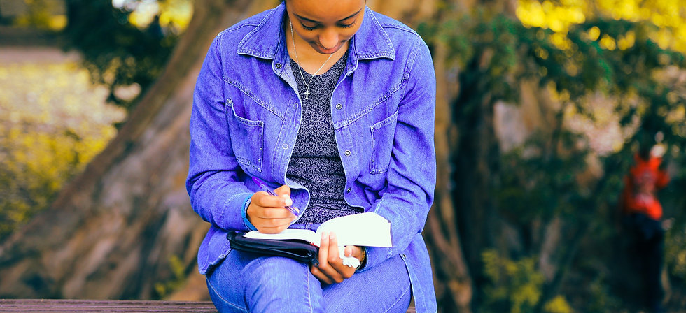 Woman reading bible while sitting outside