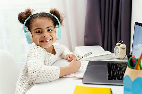 little-girl-home-during-online-school-with-laptop-headphones.jpg